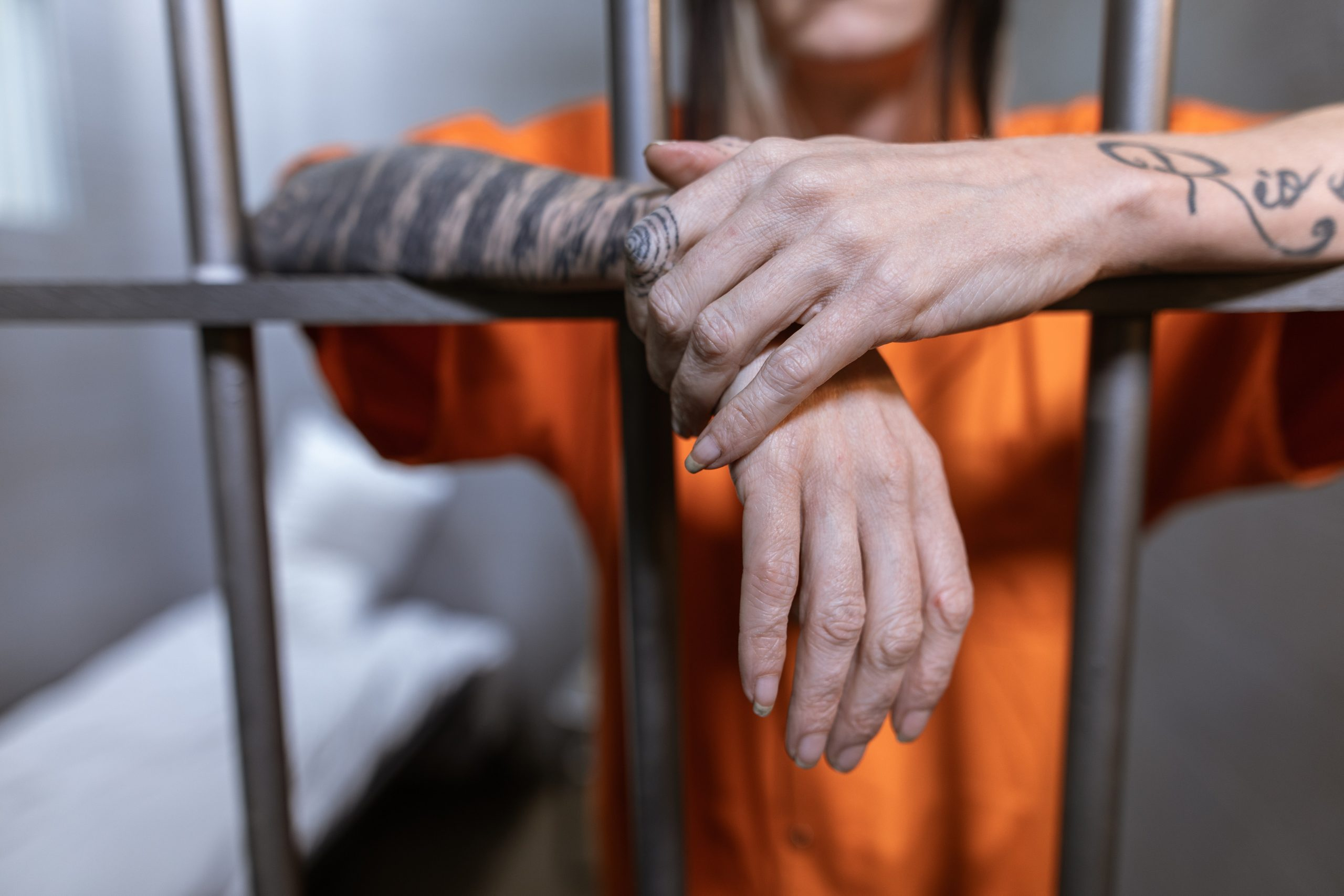 women wearing orange jumpsuit with her hands resting on jail cell bars